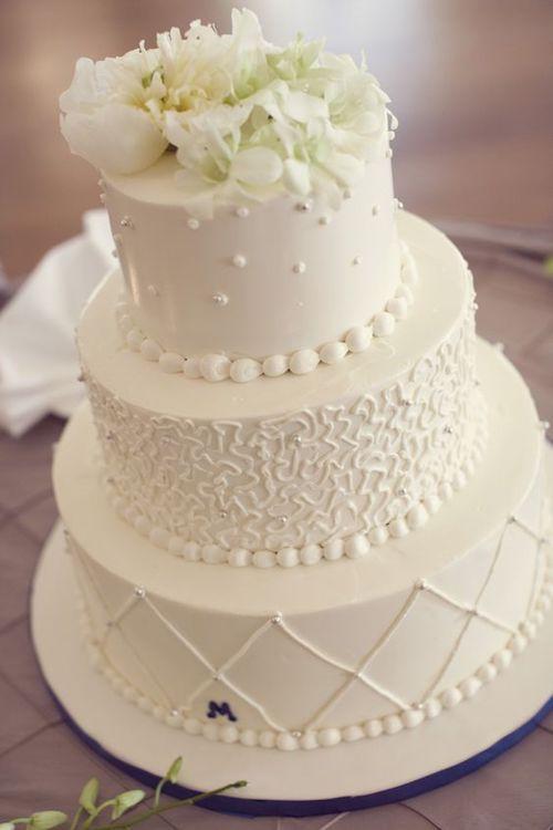 Un clásico en crema de mantequilla. Los pasteles de boda blancos siempre causan sensación.