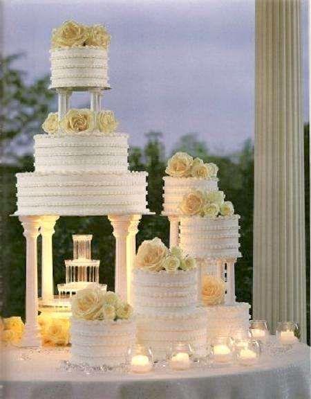 Pasteles de boda blancos en cascada con una fuente de agua y delicadas rosas té.