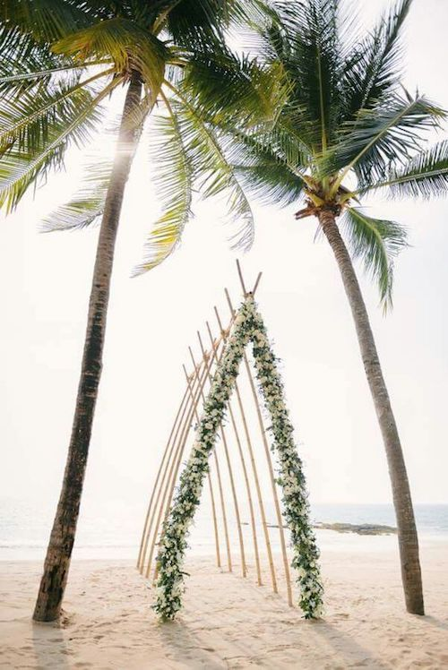 Interlaced bamboo poles and a lovely flower garland make up for a wedding arbor that is fire. Make sure you secure the poles deep inside the sand.