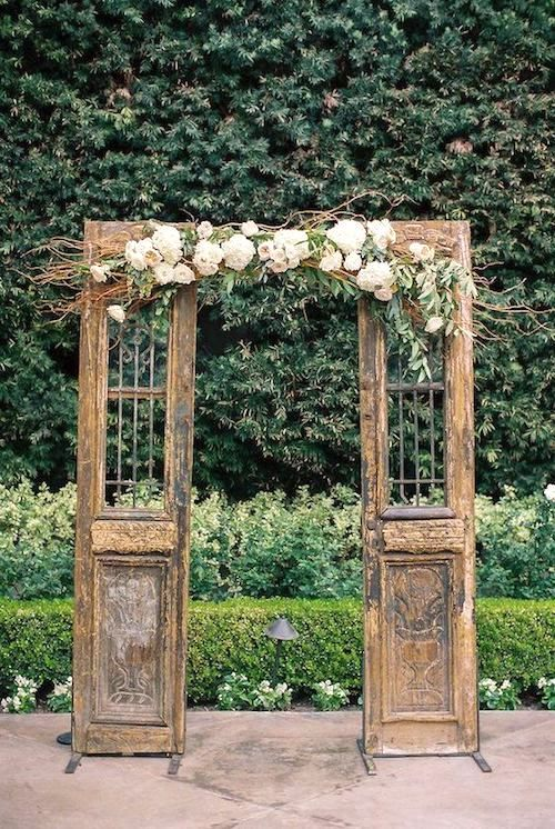 Original wooden doors with center florals for a ceremony arch.