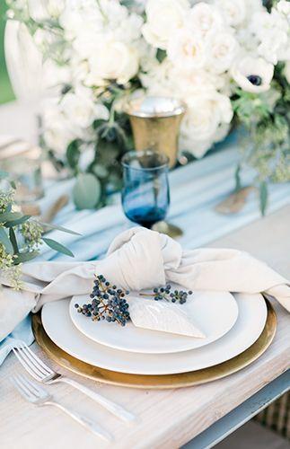 Moderna y azul. Un posaplatos en dorado, una servilleta con nudo y frutos y copas en azul para una boda junto al mar en Manhattan Beach, California.