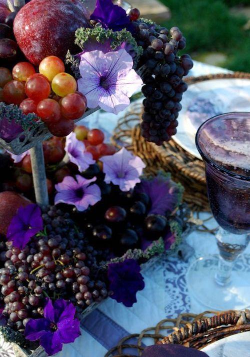"""Centro de mesa con frutas y flores en tonos morados. Ciruelas, petunias y uvas para una cena """"al fresco""""."""