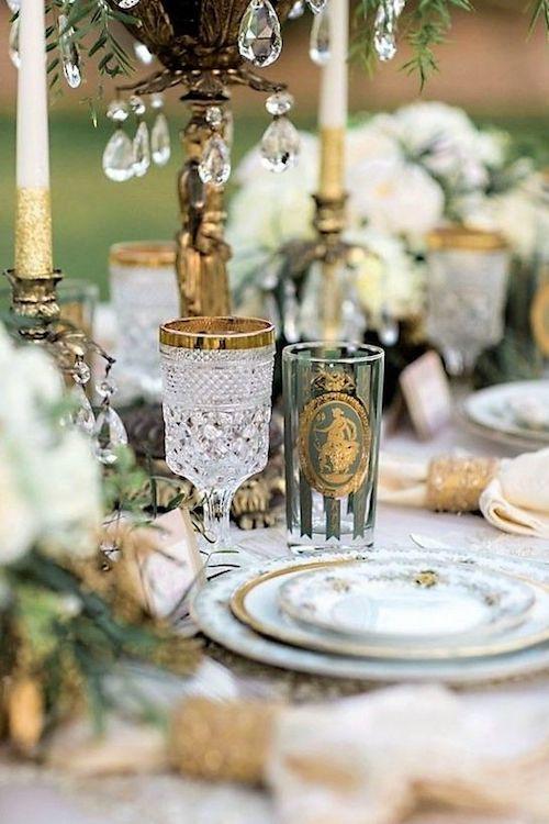 Elegancia total con copas de cristal con oro y un juego de platos de porcelana. Nota el detalle de las velas y los caireles.
