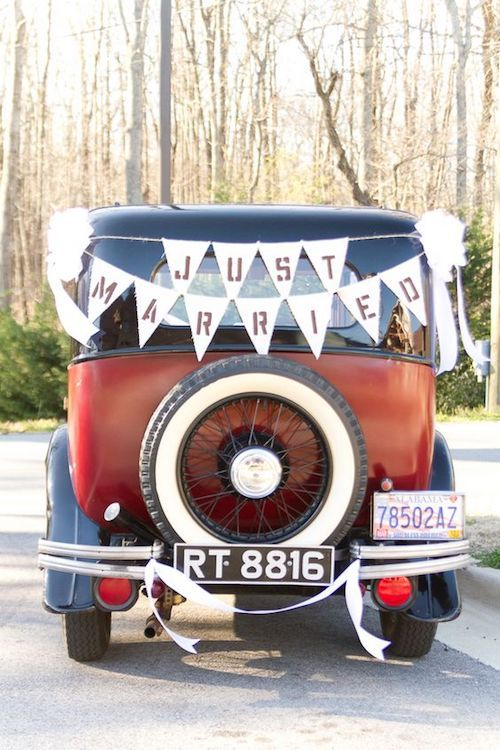 """A rustic chic departure with """"just married"""" bunting on the car."""