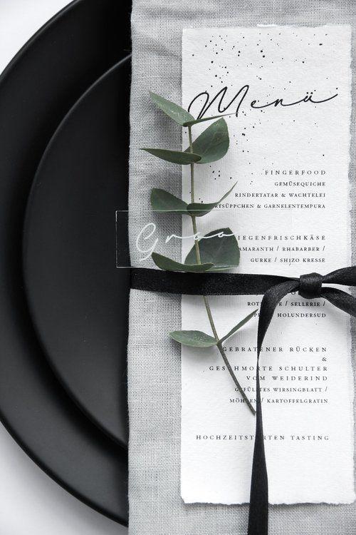 Platos en negro, servilleta de tela en gris, menu de bodas y el nombre de la invitada grabado en acrílico.