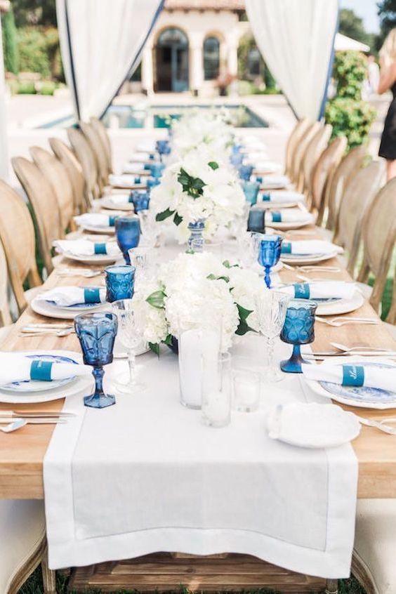 Una mesa de banquete de bodas al aire libre en beige, blanco y azul. Detalle de porta servilletas al tono. Valorie Darling Photography.