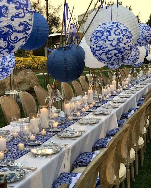 Una hilera de velas sobre un camino en azul al igual que los almohadones de las sillas. Pero los faroles se llevan el premio.