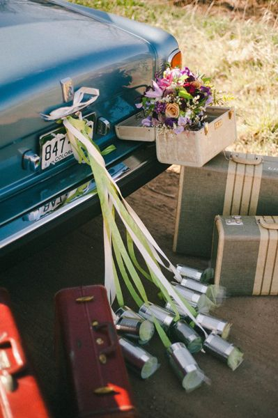 Nature and seasonal details plus the traditional tin cans adorn this vintage wedding ride.