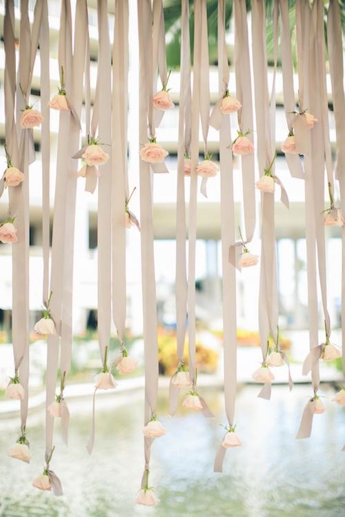 Tie some flowers at the end of the backdrop ribbons for a more romantic and unexpected look.