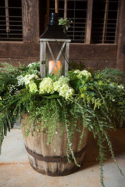 Un barril, helechos y un farol para la decoración de una boda en el patio trasero de casa, muy económica.