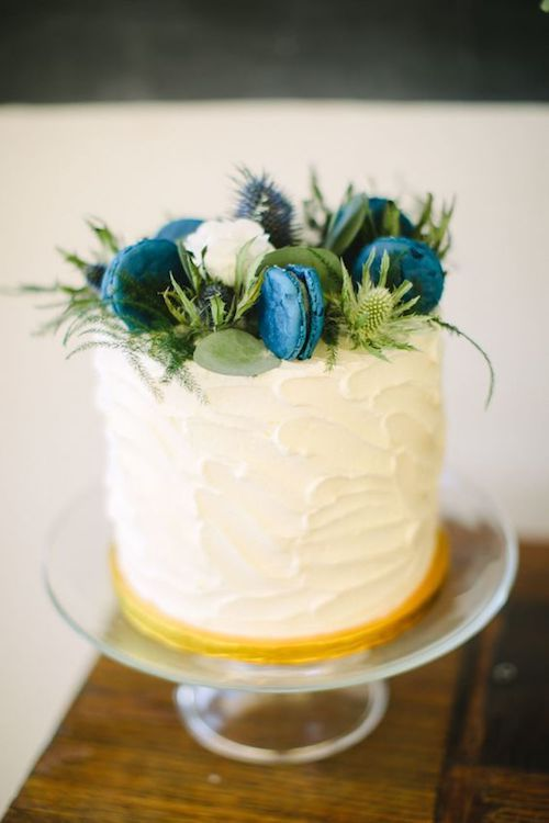 Single tiered buttercream wedding cake topped with thistles and blue macarons.