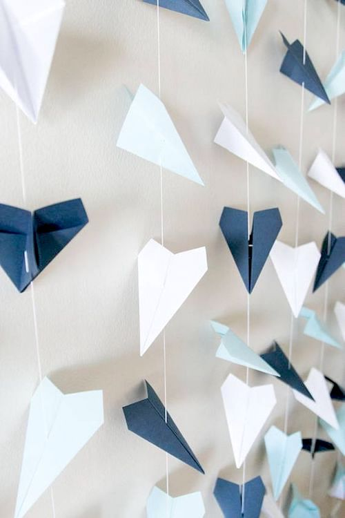 Paper airplane garlands make for original wedding backdrops to traveling couples or pilots.