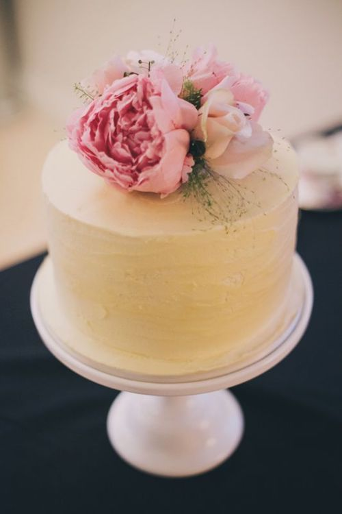 Simple wedding cake with a peony topper.