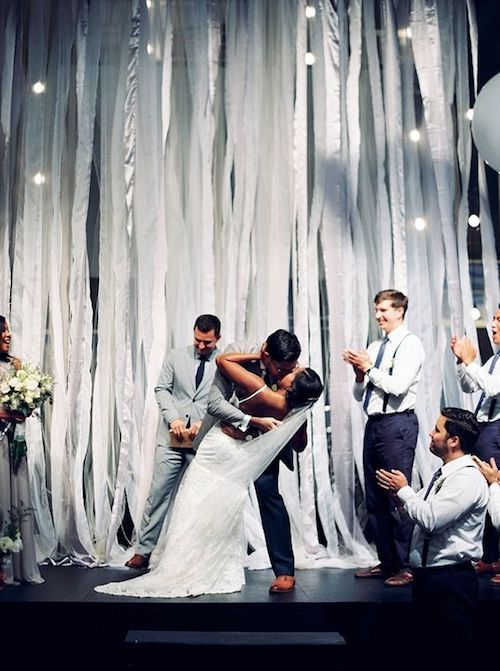 Giant white balloons float atop this breathtaking silver streamer ceremony backdrop in Richmond, VA. Kim Stockwell Photography.