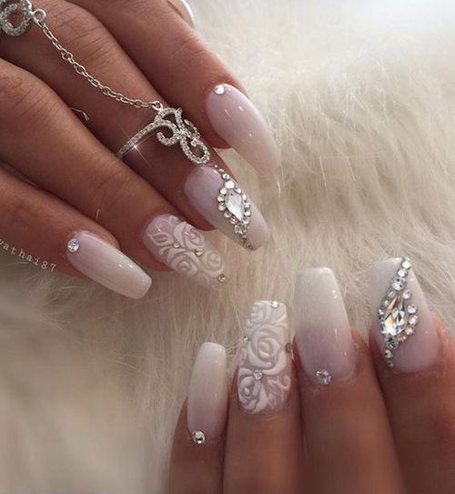 Las novias tienden a llevar uñas blancas en el día de su boda. Súmales detalles como una uña acento con diseño de rosas. Uñas decoradas muy glam.