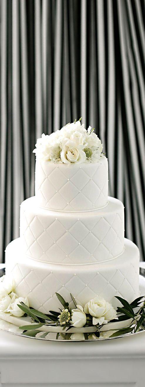 Diseños sobre fondant para una torta de tres pisos con flores frescas.