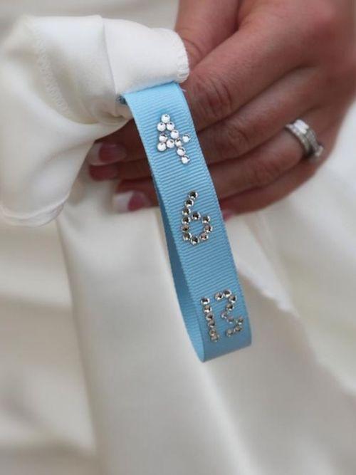 Cose un lazo azul con la fecha de la boda dentro de tu vestido.