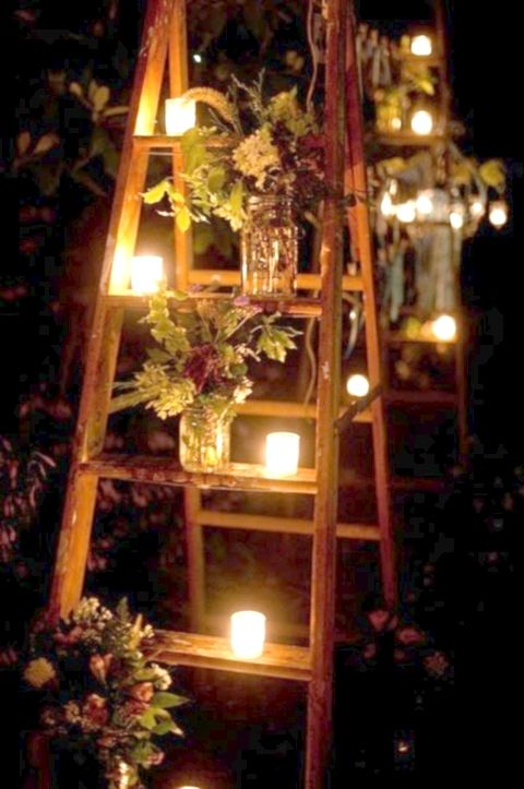 Achieve a rustic or vintage look with a ladder, votive candles and flowers in mason jars. Simple backyard wedding ideas.