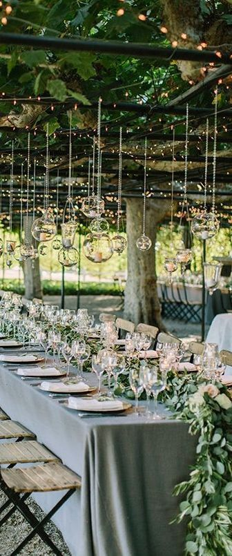 Love this gorgeous tablescape for a backyard wedding. The greenery garden, string lights and plenty of glasses!