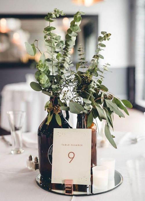 Show off your modern and unconventional side with a beer bottle and eucalyptus wedding centerpiece idea. Photo: Manayunk Brewery.