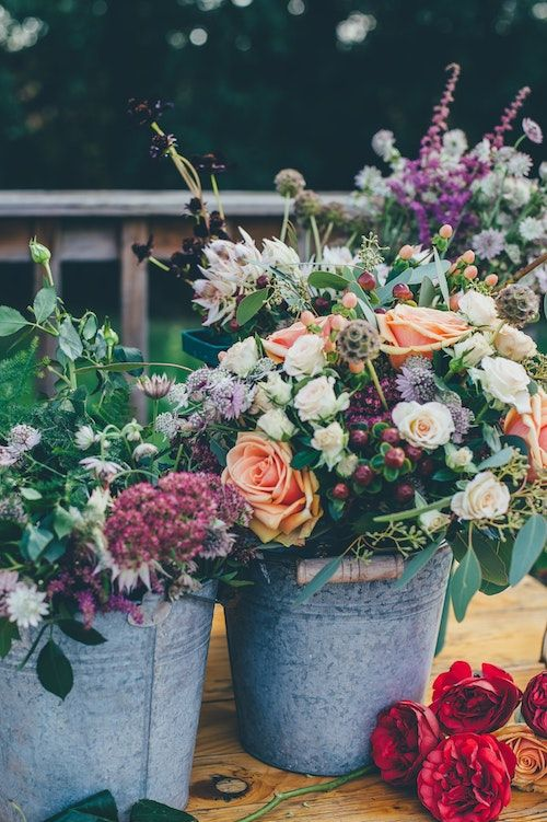 Gray buckets with flowers can turn into lovely floral arrangements at your wedding. Photo: Annie Spratt/BYW @anniespratt