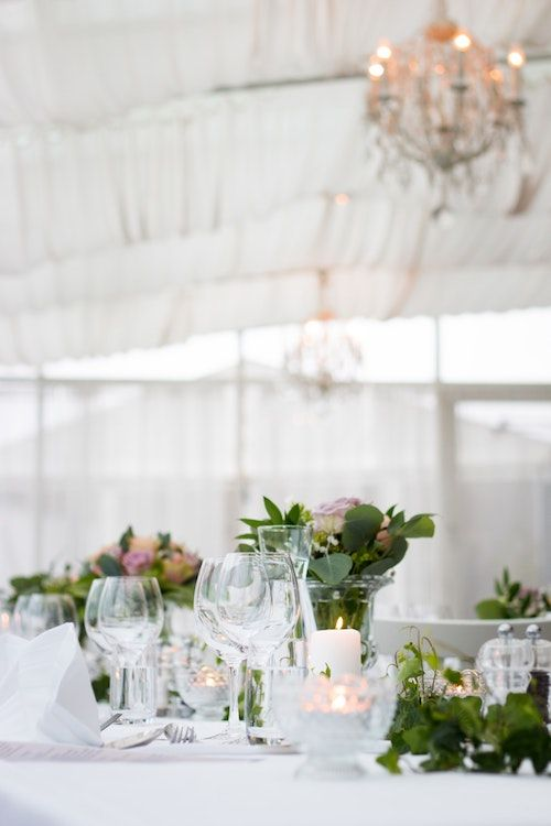 Highlight your greenery centerpieces and light fixtures with elegant light gray linens. Photo: Evelina Friman/BYW @evelinafriman