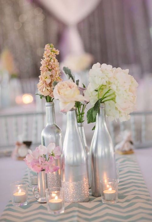 Bottles, silver paint, dust some glitter and some seasonal flowers and you have a wedding table centerpiece that will dazzle your guests!