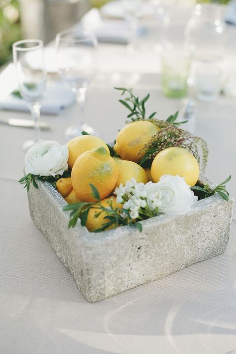 Simple and summery gray centerpiece with fresh lemons and ranunculus.
