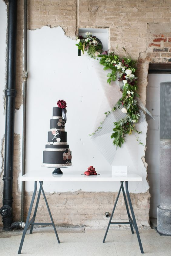 Unfinished paint and exposed brick need only some greenery and a fold up table to feature this dark gray wedding cake.