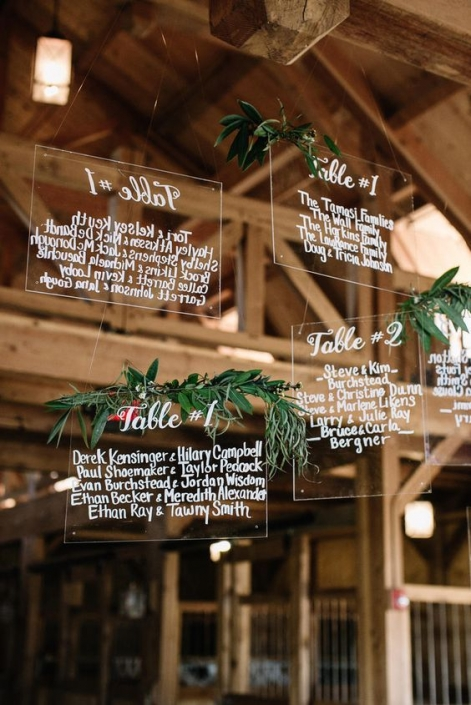 Amazing and original hanging acrylic seating charts with greenery.