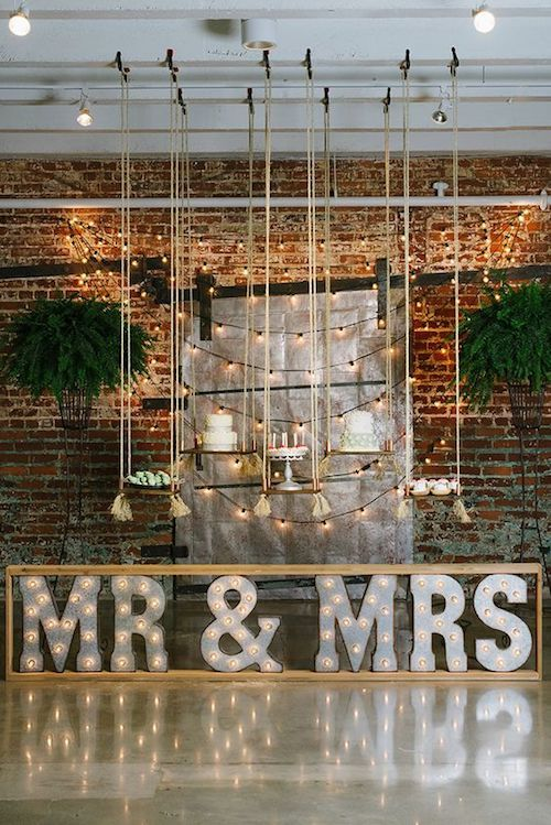 We are obsessing over this industrial themed wedding dessert table. Every detail screams modern and cool, from the hanging shelves to the Edison bulbs and the lit Mr and Mrs sign, right? Photo: Christiansen Photography.