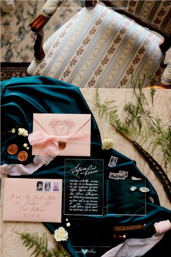 Tones of rich teal and pale blush envelopes. The invitations are clear, with an elegant white font, keeping the theme of simple elegance while adding a modern fresh twist — by Bwedding.