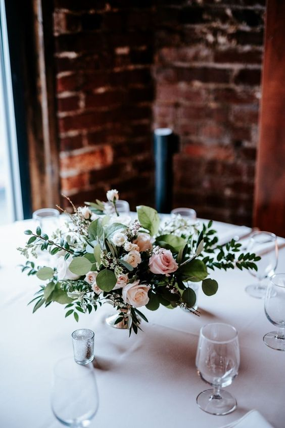 Getting married in Nashville, Tennessee? Check out One Cannery, an intimate industrial downtown wedding venue. Garden-inspired floral centerpieces meet dark and moody exposed brick walls.