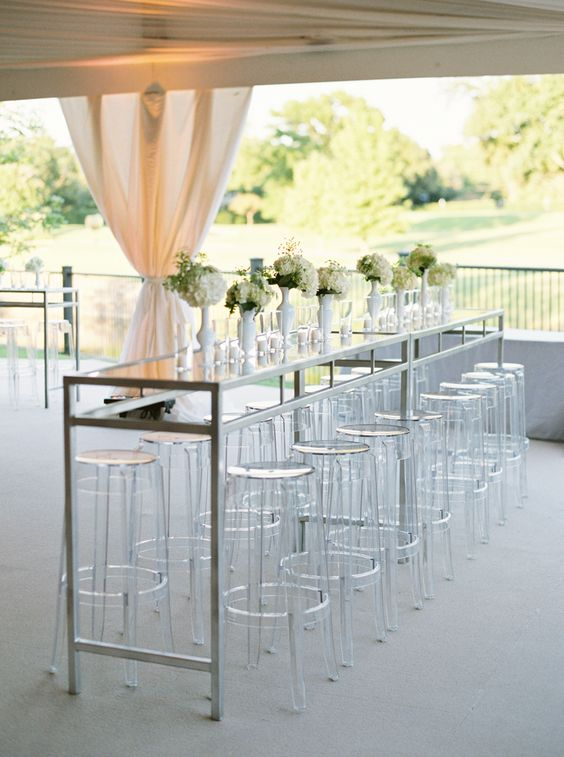 Romantic outdoor tented wedding reception with plexiglas tall chairs that blend perfectly with this timeless design.