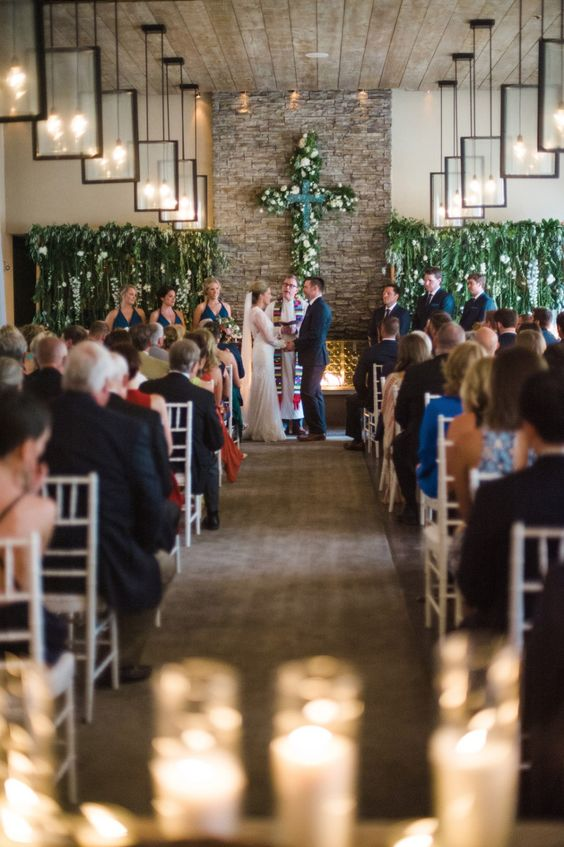 Exposed brick, wooden floor and ceilings and a whole lot of greenery at this Four Seasons Santa Fe Rancho Encantado religious ceremony in Santa Fe, New Mexico.