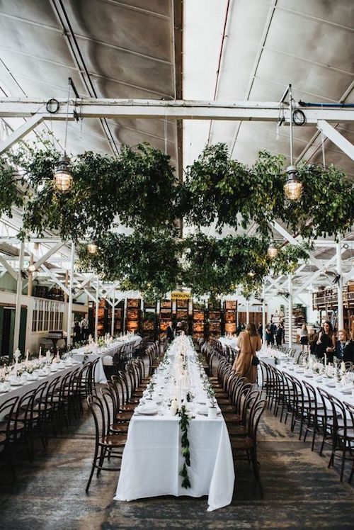 Urban feel warehouse wedding with hanging greenery. Simple, sober and woke.