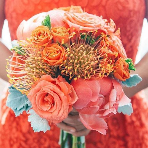 Awe-inspiring wedding bouquet. Orange and yellow flowers highlight the undertones of the living coral blooms.
