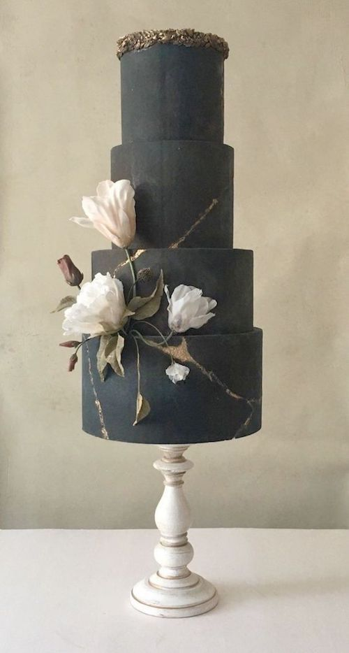 The subtle elegance of a black wedding cake crowned with gold leaves featuring an artsy flower detail.