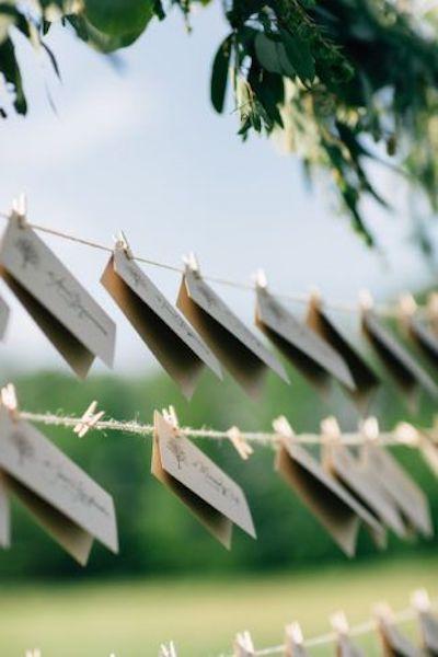 El nombre de cada invitado y su mesa atado a sogas con mini broches para una boda con reminiscencias rústicas.