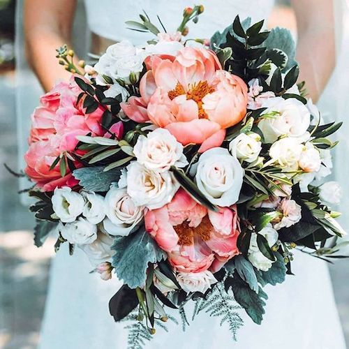 Bridal bouquet with peonies, ranunculus, garden roses, dusty millers, ferns and eucalyptus leaves.