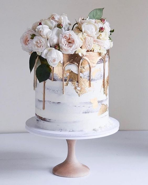Half-naked white gold drip cake topped with ranunculus for the most Pinterest-worthy winter wedding ideas.