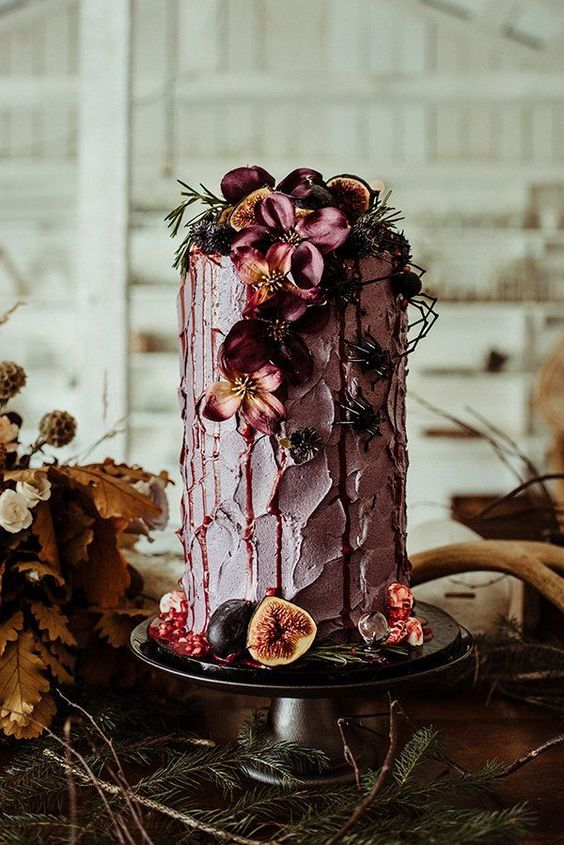 Fall inspired Uber-tall single tiered purple wedding cake surrounded with figs and berries, topped with fresh seasonal flowers and light greenery.