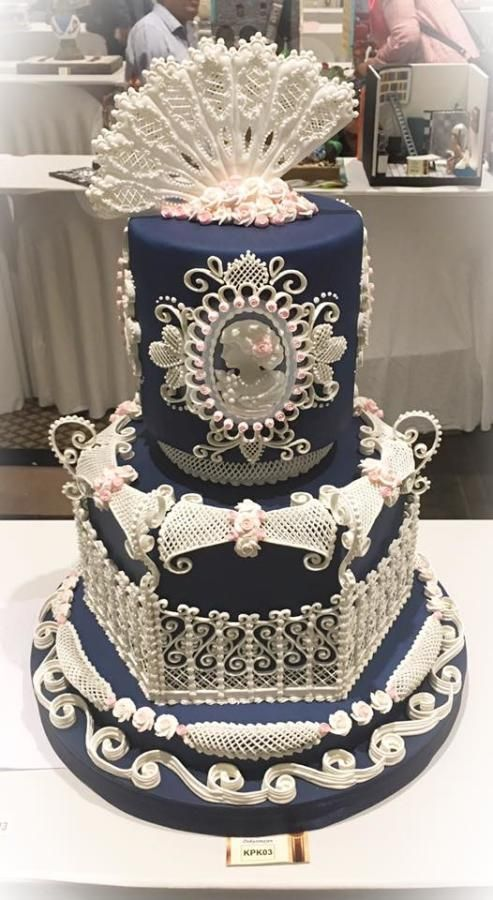 Talk about intricate design. Exquisite and delicate piping that even includes a cameo on this elegant blue wedding cake.