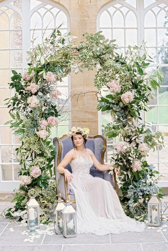Ethereal bride surrounded by the most gorgeous floral and greenery ceremony arch.