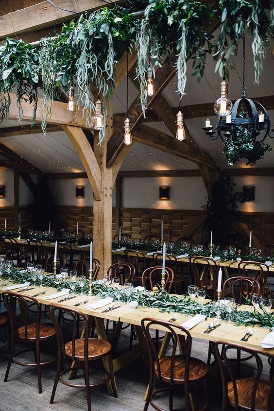 This whole vibe is great! Foliage garlands and light bulbs hanging from exposed beams.