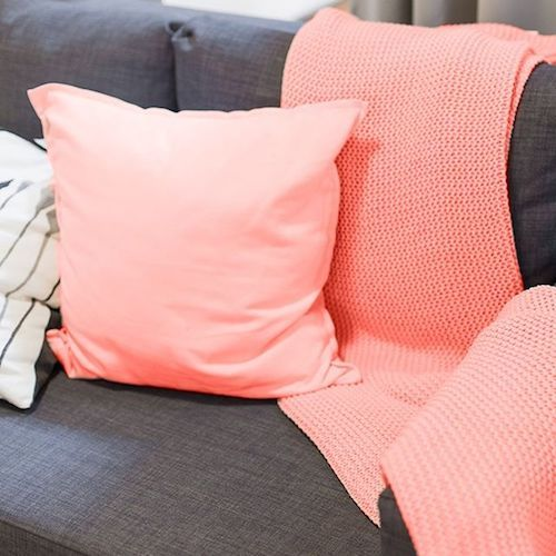 Thinking of an intimate at home wedding? Add a throw and a pillow in coral to your living room area and be on trend.
