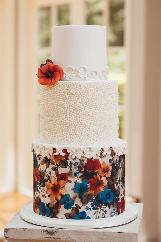 Multi-tiered confection with texture, rosette garlands and hand painted florals. By A Little Cake Place.