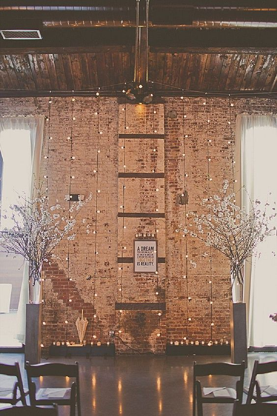 New York winter wedding ideas packed with glam and magic. All it takes is twinkle lights over exposed brick and a couple of white flower arrangements to decorate the ceremony area. Stacy Paul photography.
