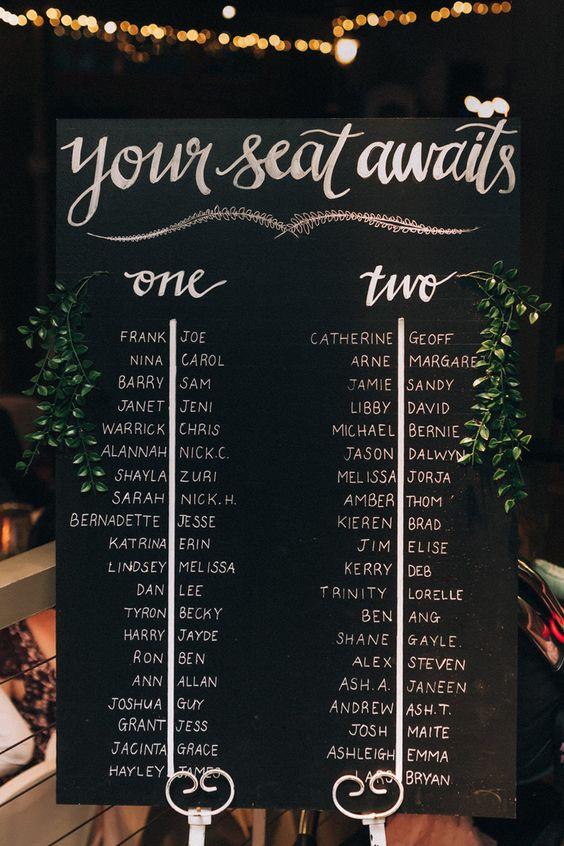 Ahorra en cartelitos con nombres en tus mesas largas con una pizarra que indica donde se sienta cada invitado a tu fiesta de matrimonio. Sigue estas reglas para una recepción animada y divertida. Fotografía: Raconteur Photography.