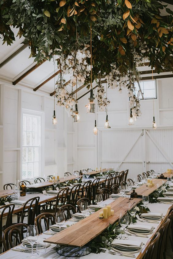 Elevated wooden table runners float towards the living ceiling floral and hanging bulbs display. Rustic boho winter wedding ideas. Photo via hellomay.